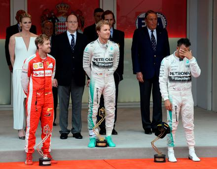 King Lewis the Third: Lewis Hamilton does his best to hide on the podium but two German chaps seem quite happy