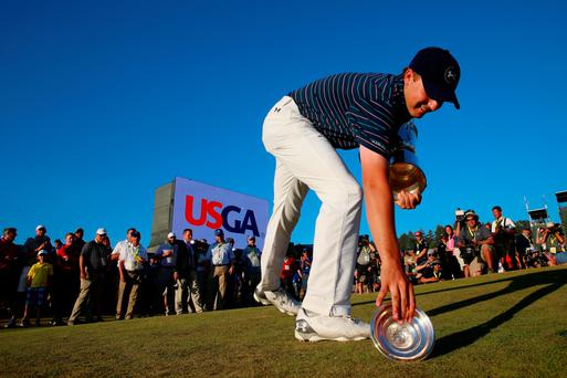 Feeling green: Disaster strikes as Jordan Spieth drops the lid of the US Open trophy causing several thousands of dollars worth of improvements to the green