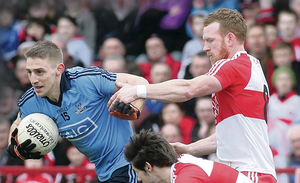Derry's Chrissy McKaigue and Fergal Doherty stop Dublin's Eoghan O'Gara in his tracks last month