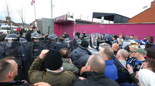 Stand off: A loyalist flag protest is met by police outside Seaview last year but scenes of tension at Irish League games have dramatically dropped over the past 20 years