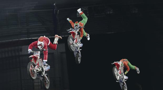 Entertainers: Supercross star Dan Whitby wears a Santa suit as Aaron Rowley and Sauson Eaton appear as his elves to launch the Arena Cross show at the Odyssey
