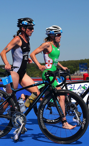 Nicky Samuels of New Zealand, left, and Aileen Reid of Northern Ireland during the transition between cycling and running in the Women's Triathlon final at Strathclyde Country Park