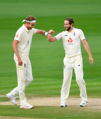 All smiles: Chris Woakes celebrates with Stuart Broad after taking Shannon Gabriel's wicket