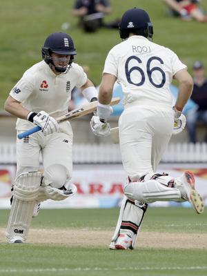 England's Ollie Pope, left, and teammate Joe Root run between the wickets (Mark Baker/AP)