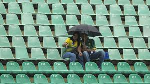 Cricket fans huddle under an umbrella as the rain holds up play in Durban (Themba Hadebe/PA)