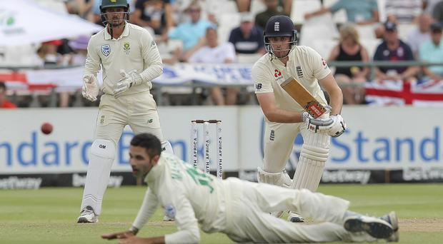 Dom Sibley drives past Keshav Maharaj, front, on his way to 85 not out (Halden Krog/AP)