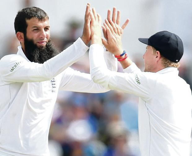 Howzat: England bowler Moeen Ali (left) is congratulated by Joe Root after taking the wicket of India's Stuart Binny at Trent Bridge