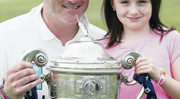 Just champion: Instonians captain Neil Russell lifts the league trophy while his eight-year-old daughter Evie joins in the celebrations