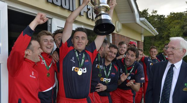 Silver lining: Waringstown captain Lee Nelson lifts the Irish Senior Cup aloft after his side lifted the trophy and were also crowned Ulster Senior League champions on the same day