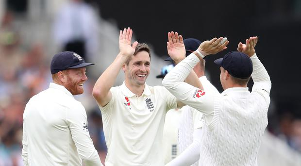 Chris Woakes, centre, celebrates England's early breakthroughs against India (Tim Goode/PA)
