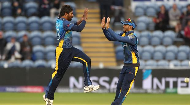 Sri Lanka's Nuwan Pradeep celebrates taking the wicket of Afghanistan's Rashid Khan with Dhananjaya de Silva during the ICC Cricket World Cup group stage match at the Cardiff Wales Stadium.