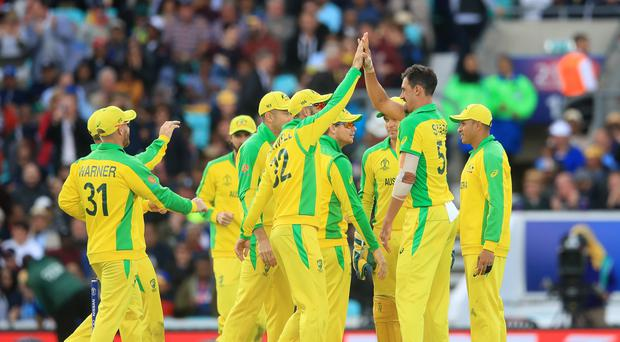 Mitchell Starc, second right, celebrates with his teammates as Australia go top of the World Cup standings (Adam Davy/PA)