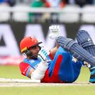 Afghanistan's Hashmatullah Shahidi lies on the ground after being struck by the ball (Martin Rickett/PA)