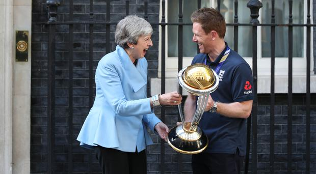 Eoin Morgan enjoys showing off England's World Cup trophy to Prime Minister Theresa May. (Yui Mok/PA)
