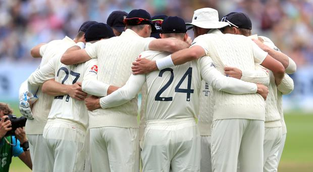England players huddle before the first ball (Mike Egerton/PA)