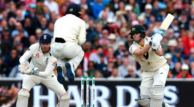 High point: England's Jos Buttler jumps as he attempts to field a shot from Australia's Steve Smith on the first day of the fourth Ashes Test