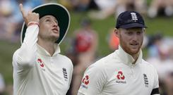 Joe Root gestures as he walks with Ben Stokes (Mark Baker/AP)