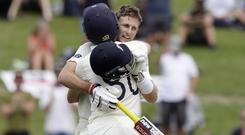 England's Joe Root, right, is congratulated by teammate Ollie Pope (Mark Baker/AP)