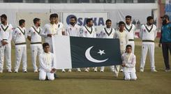 Pakistani players stand for national anthem before start the game of first day of 1st cricket test match between Pakistan and Sri Lanka, in Rawalpindi, Pakistan, Wednesday, Dec. 11, 2019. (AP Photo/Anjum Naveed)