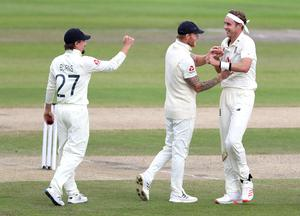 England's Stuart Broad, right, celebrates with Ben Stokes and Rory Burns (Martin Rickett/PA)