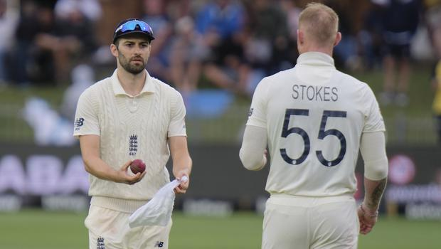 Mark Wood gives the ball to team-mate Ben Stokes to dry on day two (Michael Sheehan/AP)