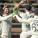 England's players celebrate on the fourth day of the fourth Test against South Africa (Themba Hadebe/AP)