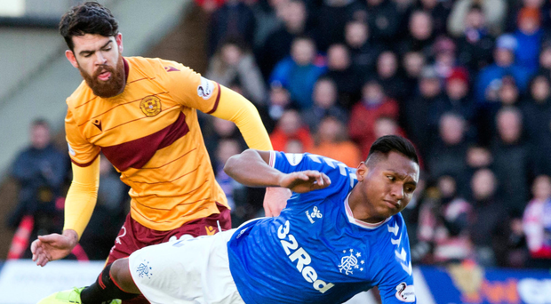 Going down: Alfredo Morelos is felled by Well's Liam Donnelly