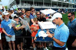 Sign here: Rory McIlroy delights some autograph hunters at Sawgrass yesterday