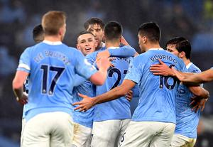 Manchester City players gather to celebrate Phil Foden's goal against Brighton on Wednesday evening (Laurence Griffiths/PA)
