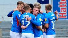 In his Pomp: Ronan Curtis is mobbed by his Portsmouth team-mates
