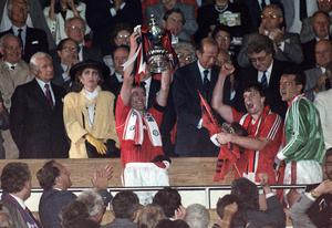 Manchester United captain Bryan Robson holds up the FA Cup in 1990 (PA)