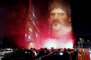 Fans light flares as they gather under a mural depicting Maradona in Naples (Fabio Sasso/AP)
