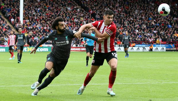 Sheffield United centre-back John Egan, pictured battling for the ball against Liverpool's Mo Salah, is a doubt for the match against Manchester United due to a clash of heads while on Republic of Ireland duty (Richard Sellers/PA Images).