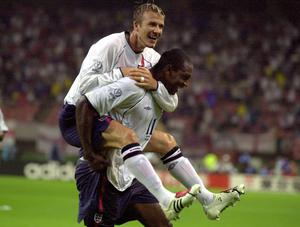 Emile Heskey is embraced by David Beckham after scoring England's third goal against Denmark in 2002 (Rui Vieira/PA).