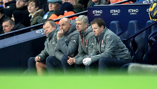Arsenal manager Arsene Wenger sits on the bench with his coaching staff