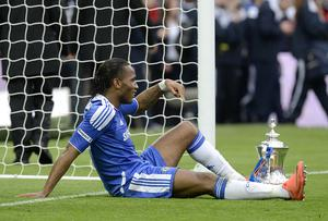 Didier Drogba, who scored Chelsea's second goal in their 2-1 win against Liverpool in the 2012 final, has a rest during post-match celebrations (Rebecca Naden/PA)