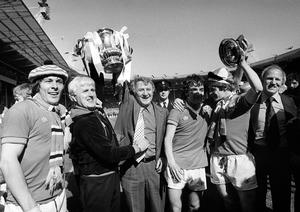Manchester United manager Tommy Docherty (third from left) celebrates with players and staff after FA Cup final victory over Liverpool at Wembley in 1977 (PA)