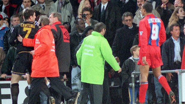 Cantona is escorted off the pitch after lunging at a fan in the crowd at Selhurst Park (PA Archive)