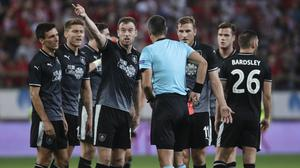 Ashley Barnes, left, gestures as players argue with the referee following Ben Gibson's red card (Petros Giannakouris/AP)