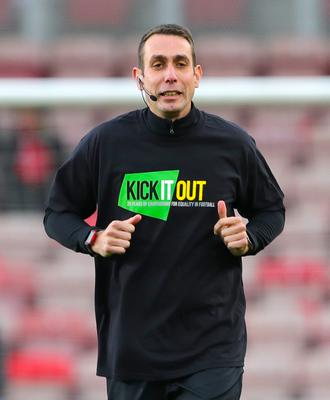 Referee David Coote warms up in a Kick It Out t-shirt as part of a campaign that has raised awareness of racism in the game (Richard Sellers/PA)