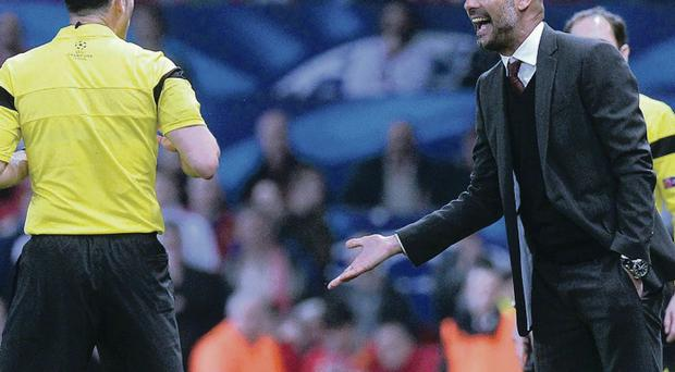 Bayern Munich's Pep Guardiola argues with referee Carlos Velasco Carballo ater he gave a red card to Bayern Munich's Bastian Schweinsteiger