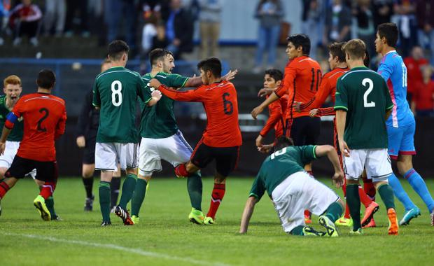 Kick up the backside: Northern Ireland's Tom Smart is on the receiving end from Mexico's Carlos Alberto Arreola