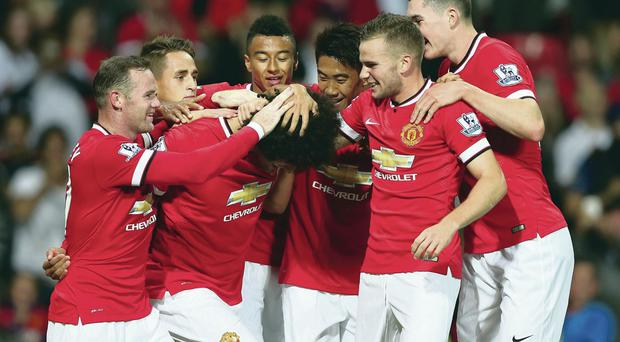 Ahead of the game: Marouane Fellaini gets his hair ruffled by team mates after scoring Manchester United's winner