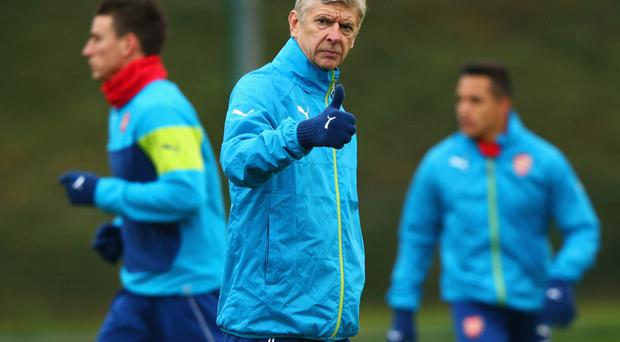 Thumbs up: Arsene Wenger oversees Arsenal training yesterday after hearing he has Laurent Koscielny available again