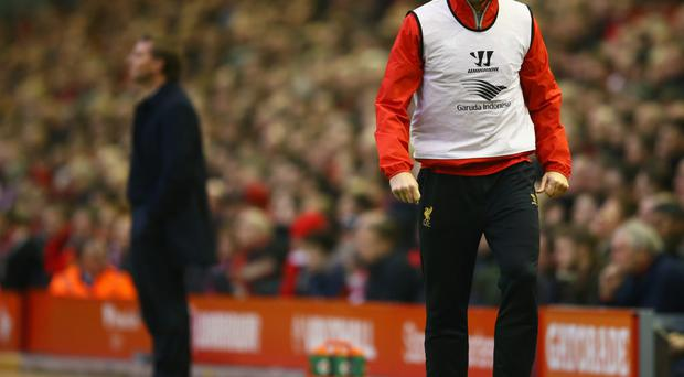 Different directions: Steven Gerrard warms up on the touchline on Saturday, with Liverpool manager Brendan Rodgers in the background