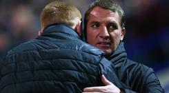 Close pals: Liverpool boss Brendan Rodgers embraces his Bolton counterpart, Neil Lennon, at the finish