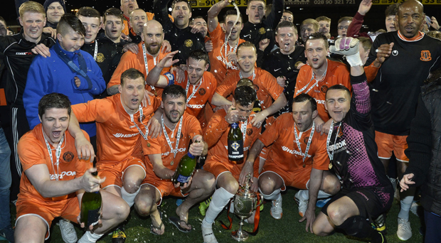 Just champion: Carrick Rangers players celebrate after lifting the Intermediate Cup to complete the treble