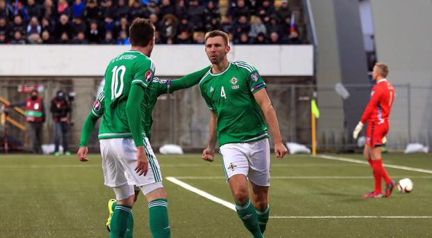 Gareth McAuley, right, celebrates nodding in his second of the night