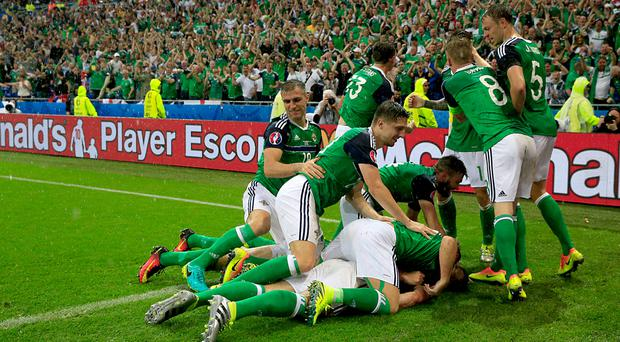 Gareth McAuley, bottom, was mobbed by Northern Ireland players having scored against Ukraine