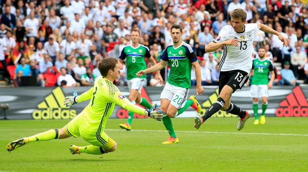 Michael McGovern, left, saves from Thomas Muller in the first half